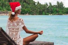 Jovem mulher no chapéu do Natal que medita em uma pose da ioga fotos de stock
