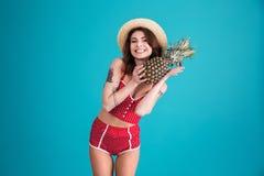Jovem mulher no chapéu do roupa de banho e de palha que guarda o abacaxi fresco Fotografia de Stock