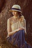 Jovem mulher no chapéu retro que senta-se na grama fotografia de stock