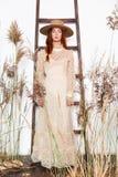 Jovem mulher no chap?u e no vestido do estilo do vintage imagens de stock royalty free