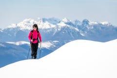 A jovem mulher no cume tanto da neve aumenta para a parte superior nas montanhas fotos de stock