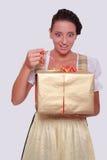 A jovem mulher no Dirndl bávaro agarra um presente de Fotos de Stock Royalty Free