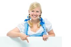 A jovem mulher no dirndl guardara o espaço do anúncio Imagens de Stock