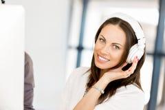 Jovem mulher no escritório com fones de ouvido Imagem de Stock