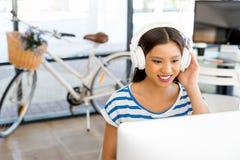 Jovem mulher no escritório com fones de ouvido Fotografia de Stock Royalty Free