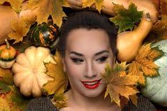 A jovem mulher no fundo das folhas e das abóboras de outono Imagens de Stock