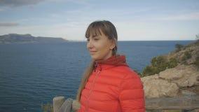 Jovem mulher no fundo do mar Fêmea moreno caucasiano de sorriso no hoodie vermelho e no revestimento da bolha que olham para a fr video estoque