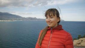 Jovem mulher no fundo do mar Menina moreno caucasiano de sorriso com cabelo de vibração no vento que olha para a frente de vídeos de arquivo