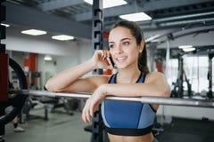Jovem mulher no gym usando o equipamento da aptidão imagens de stock royalty free