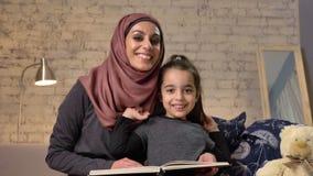 A jovem mulher no hijab que sorri e senta-se no sofá com sua filha e ensina-se lhe como ler, para registrar, conceito de família  vídeos de arquivo