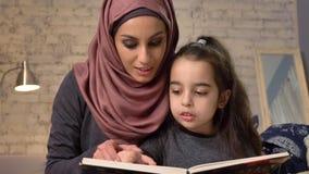 A jovem mulher no hijab senta-se no sofá com sua filha e ensina-se lhe como ler, para registrar acima, conceito de família feliz, vídeos de arquivo