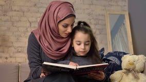 A jovem mulher no hijab senta-se no sofá com sua filha e ensina-se lhe como ler, para registrar, conceito de família feliz 50 fps vídeos de arquivo