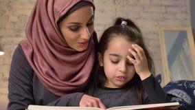 A jovem mulher no hijab senta-se no sofá com sua filha e ensina-se lhe como ler, para registrar, o conceito de família feliz, fim filme