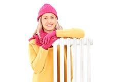 A jovem mulher no inverno veste o assento ao lado de um radiador Fotos de Stock Royalty Free