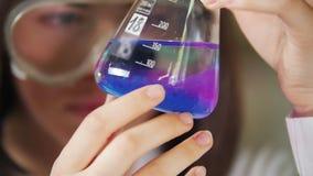 Jovem mulher no laboratório químico que guarda uma garrafa com azul e o roxo nele Foco na garrafa filme