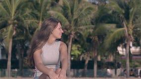 Jovem mulher no molho apertado do verão contra as palmas verdes filme