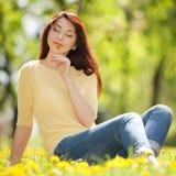 Jovem mulher no parque com flores Foto de Stock Royalty Free