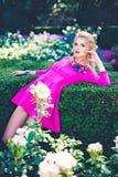 Jovem mulher no parque com os arbustos cor-de-rosa brancos Imagem de Stock