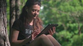 A jovem mulher no parque usa a tabuleta para o estudo e o trabalho filme