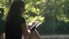 Jovem mulher no parque usando a tabuleta digital filme