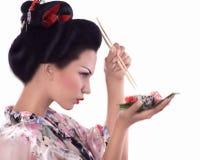 Jovem mulher no quimono japonês com hashis e rolo de sushi Fotos de Stock
