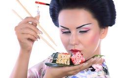 Jovem mulher no quimono japonês com hashis e rolo de sushi Foto de Stock Royalty Free