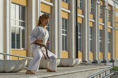 Jovem mulher no quimono que faz o exercício formal do karaté imagem de stock