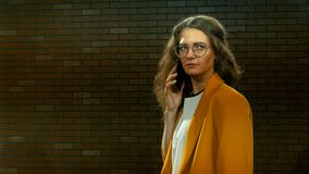 A jovem mulher no revestimento amarelo fala pelo telefone 05 filme