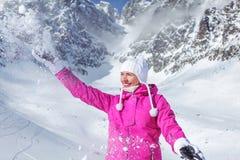Jovem mulher no revestimento de esqui cor-de-rosa e no sorriso branco das luvas foto de stock royalty free