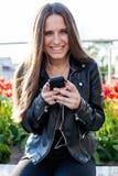 A jovem mulher no revestimento e em calças de brim pretos está sentando-se no parapeito de pedra Fotografia de Stock