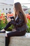 A jovem mulher no revestimento e em calças de brim pretos está sentando-se no parapeito de pedra Foto de Stock