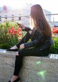 A jovem mulher no revestimento e em calças de brim pretos está sentando-se no parapeito de pedra Imagens de Stock Royalty Free