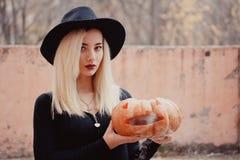 Jovem mulher no revestimento preto que guarda a abóbora do Dia das Bruxas com o fumo branco que vem do interior dele no outono foto de stock