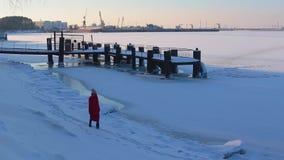 Jovem mulher no revestimento vermelho longo que anda no banco coberto de neve do rio congelado perto do cais filme