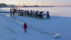 Jovem mulher no revestimento vermelho longo que anda no banco coberto de neve do rio congelado perto do cais, no fundo do porto f filme