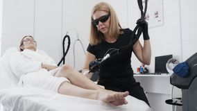 Jovem mulher no roupão branco no procedimento de remoção na clínica do esteticista, movimento lento do cabelo do laser vídeos de arquivo