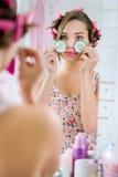 Jovem mulher no roupão com o pepino nos olhos Foto de Stock