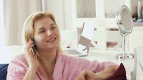 A jovem mulher no roupão doméstico fala no telefone que senta-se no sofá na sala de visitas filme