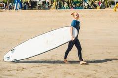 Jovem mulher no roupa de banho com ressaca para os novatos prontos para surfar P imagens de stock royalty free