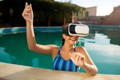 Jovem mulher no roupa de banho do biquini usando vidros impermeáveis da realidade virtual na piscina que joga o jogo Menina loura fotos de stock