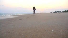 Jovem mulher no roupa de banho que corre na praia vazia do mar Menina que movimenta-se ao longo da costa do oceano Exerc?cio f?me video estoque