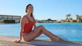 Jovem mulher no roupa de banho vermelho vermelho do corpo, perto da associação no hotel luxuoso da selva, relaxando na piscina Me vídeos de arquivo