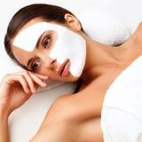 Jovem mulher no salão de beleza dos termas com máscara cosmética na cara. Fotografia de Stock