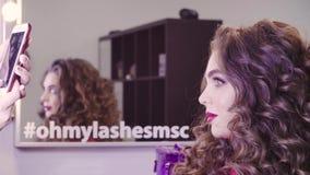 Jovem mulher no salão de beleza que olha no espelho filme
