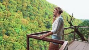 Jovem mulher no short branco claro da blusa e da sarja de Nimes do às bolinhas na ponte sobre a garganta de Okatse e fala no tele video estoque
