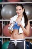 A jovem mulher no sportswear mantem uma garrafa de água foto de stock