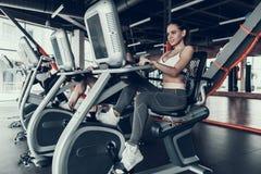 Jovem mulher no Sportswear na bicicleta de exercício no Gym foto de stock