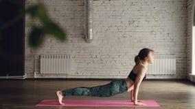 A jovem mulher no sportswear na moda está praticando a ioga durante a prática individual no centro moderno do bem-estar Está faze video estoque