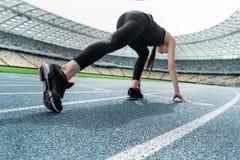Jovem mulher no sportswear na posição começar sobre o estádio da pista de atletismo foto de stock