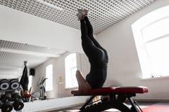 Jovem mulher no sportswear preto contratado no gym A menina faz os exercícios que estão nas omoplatas no gym fotografia de stock royalty free